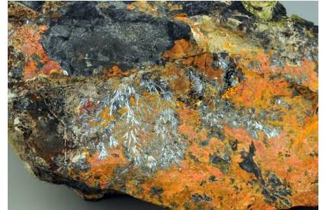 Antimonit als fiederartige, metallgrau glänzende Aggregate in orangerotem Realgar (Lojane, Mazedonien); Foto: A. Schumacher, NHM Wien