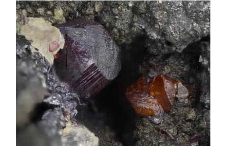 Der Ausschnitt zeigt orange Xanthokon-Kriställchen und einen dunkelroten, kurzprismatischen Proustit-Kristall.  Bildbreite 5,8 mm; Foto: H. Schillhammer, NHM Wien