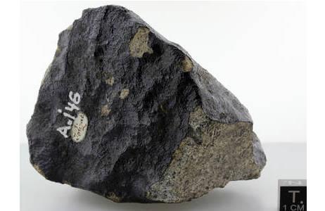 Bruchstück des Jonzac Meteoriten (Inventarnr: A146) mit gut erhaltener Schmelzkruste. Jonzac gehört zur Gruppe der sogenannten Eukrite und ist ein beobachteter Meteoritenfall in Frankreich aus dem Jahr 1819. Das hellgraue Gestein hebt sich stark von der schwarz glänzenden Schmelzkruste ab und beherbergt neben zahlreichen anderen Mineralen auch mikroskopisch kleine Zirkonkörner, welcher in der typischen Größe von 0,005 . 0,02 mm mit dem bloßen Auge allerdings kaum zu erkennen sind.; Foto: NHM Wien