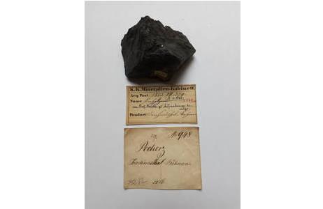 """Inventarisiertes historisches Objekt (""""Pecherz"""" = Uraninit) mit aufgeklebter Inventarnummer und originalen Etiketten (Av588).; Foto: A. Schumacher, NHM Wien"""
